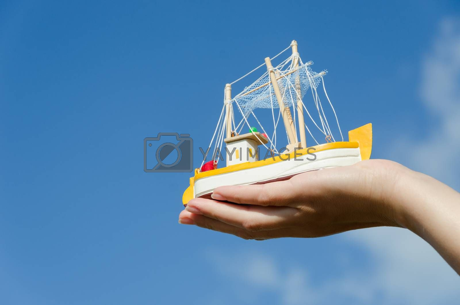 wooden retro ship miniature toy on female palm on blue sky background