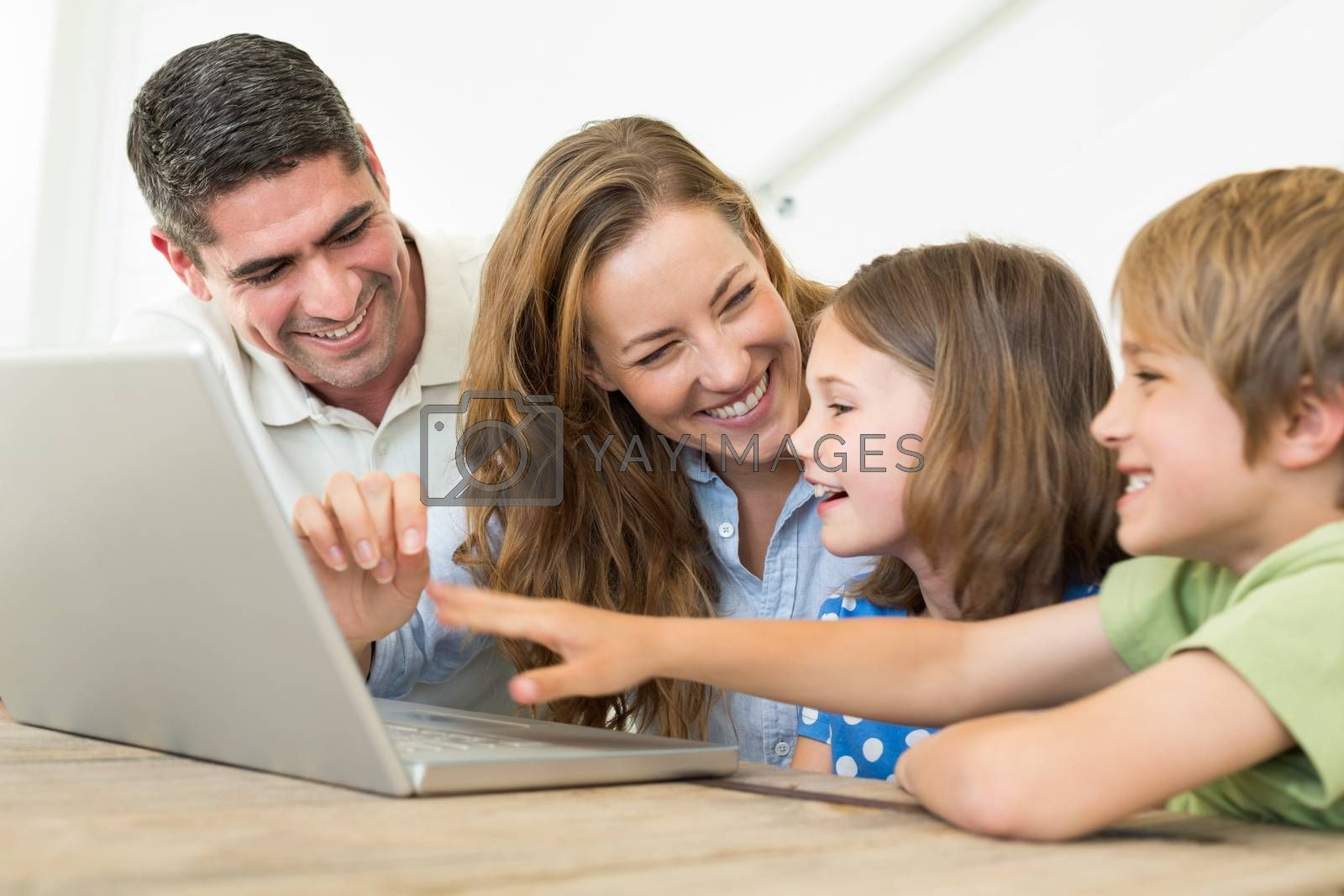 Cheerful family using laptop at home