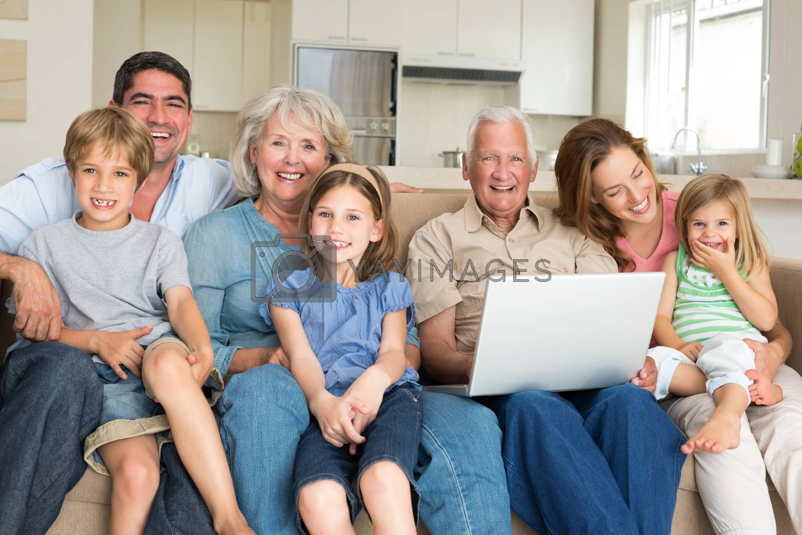 Portrait of cheerful multigeneration family with laptop in living room