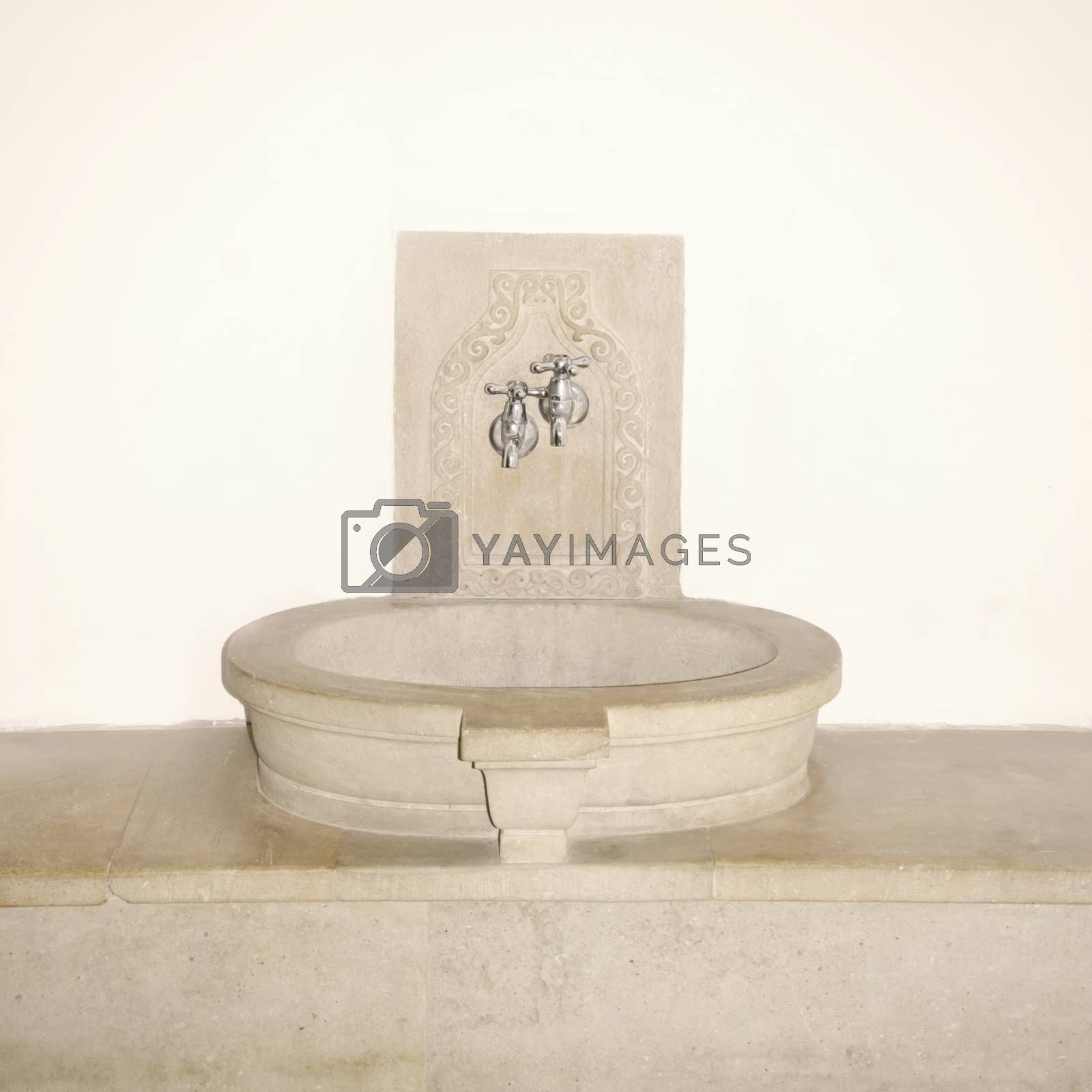 Vintage Stone Sink and Faucet Over White Wall