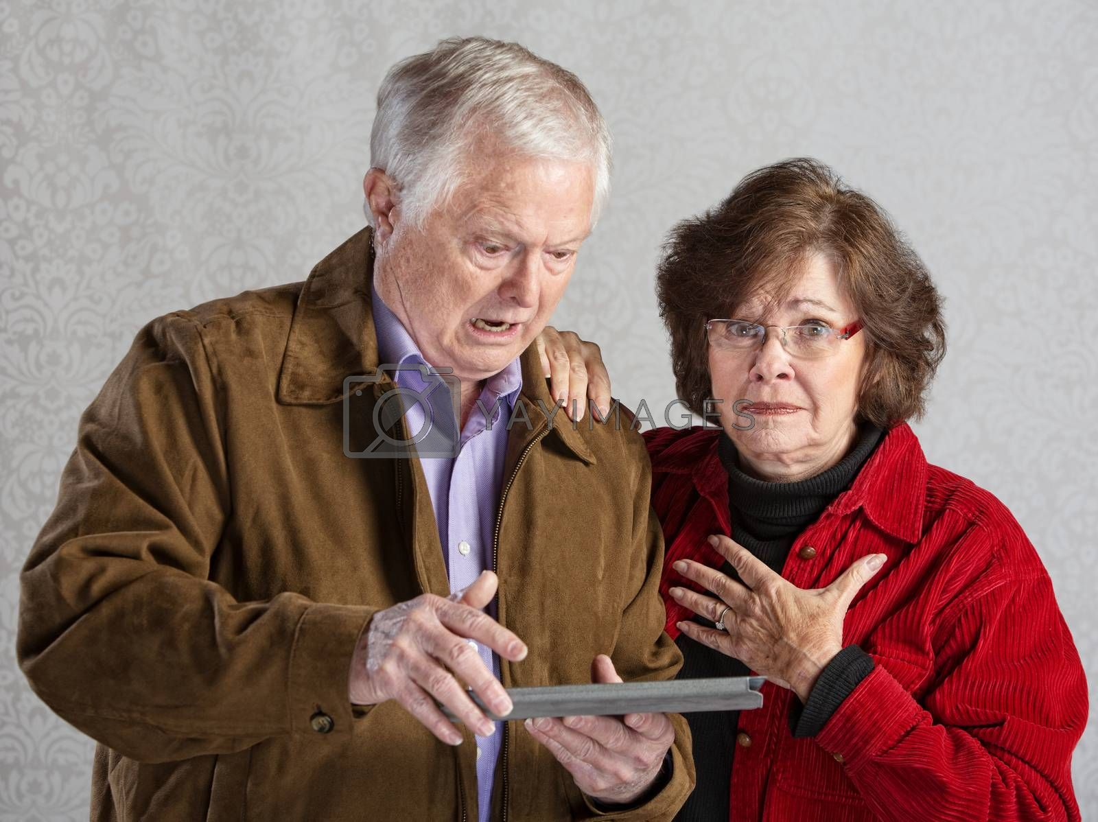 Angry man using tablet with embarrassed woman