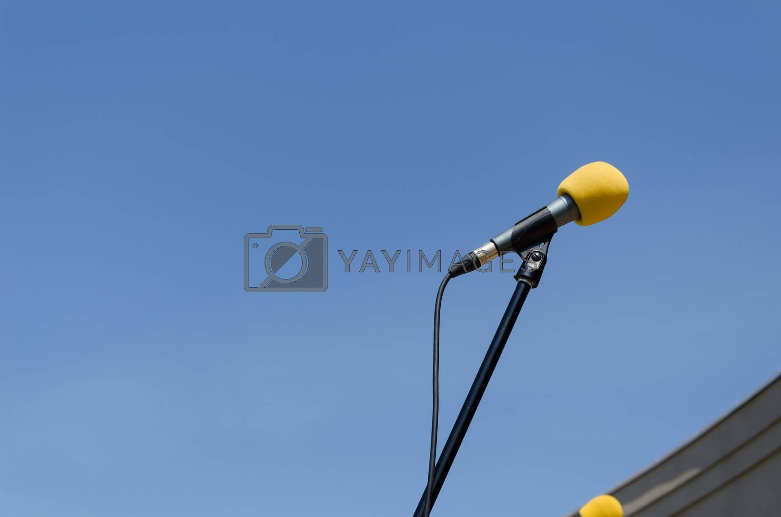 yellow microphone with stand on blue sky background