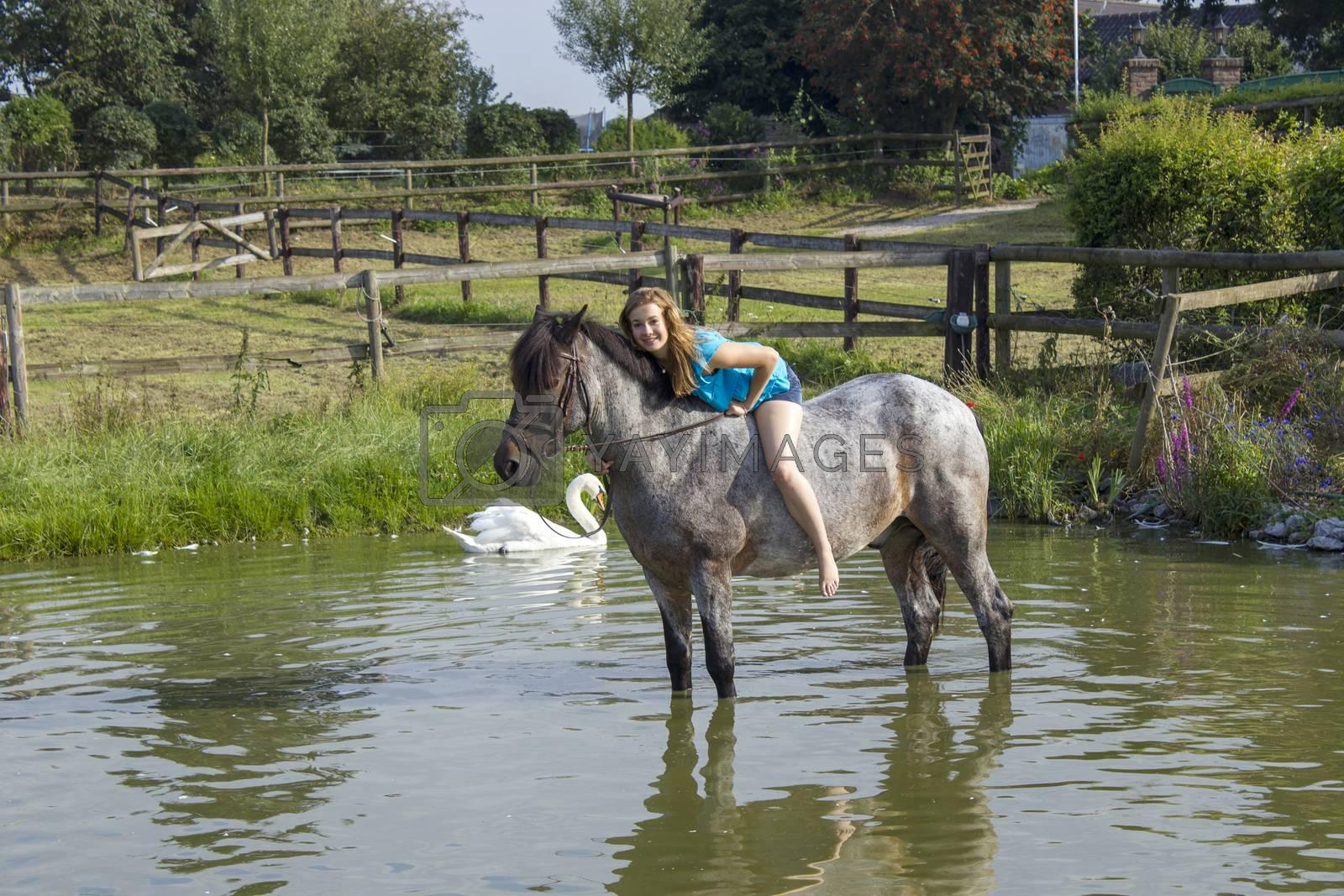 young girl riding a horse outdoors