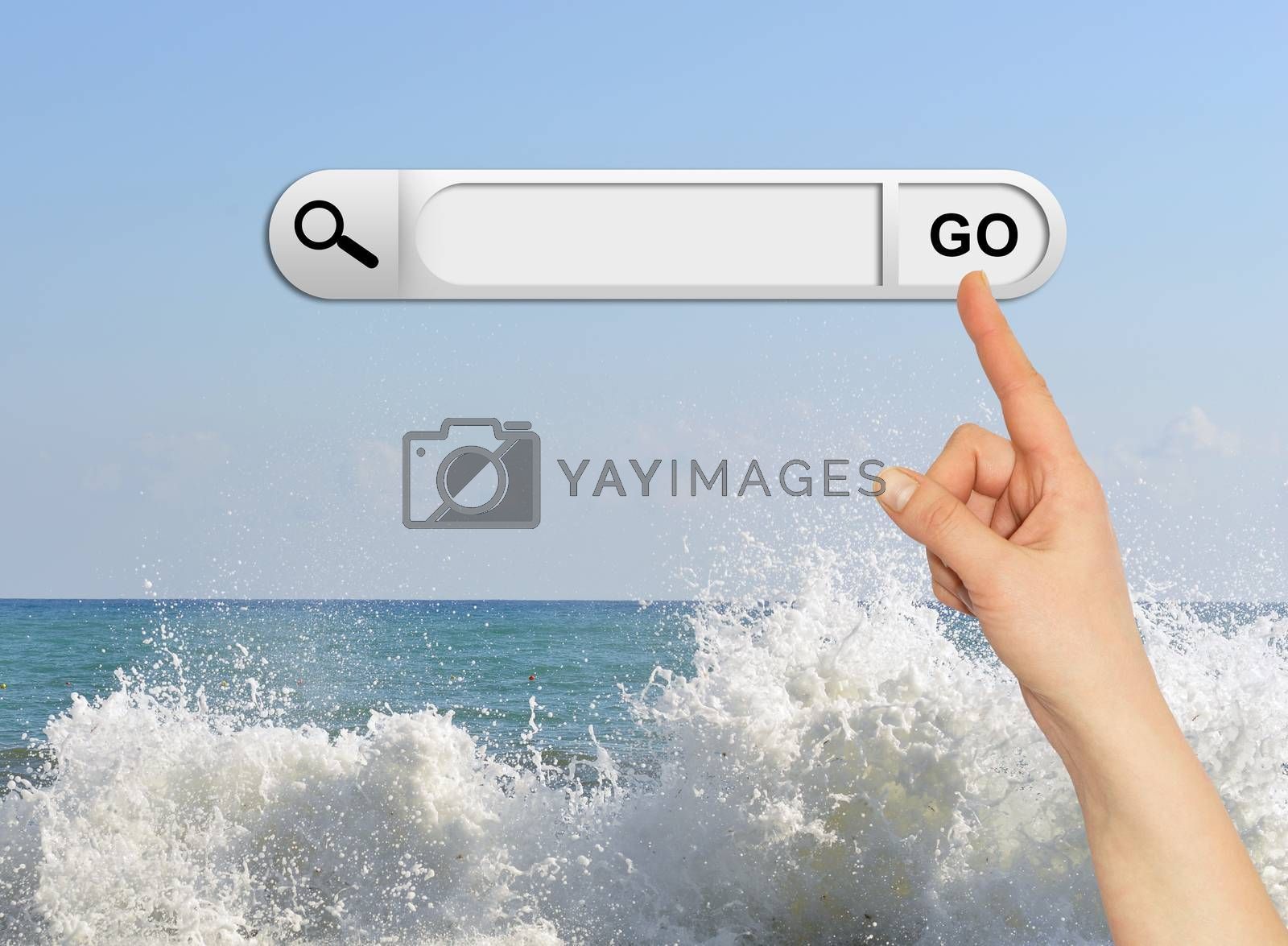 Human hand indicates the search bar in browser. Waves breaking on stony beach as backdrop