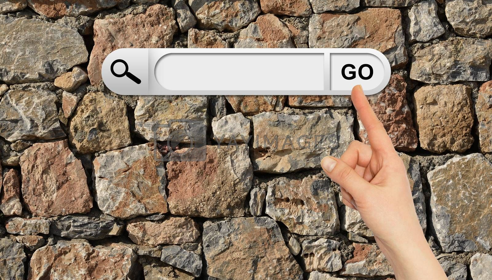 Human hand indicates the search bar in browser. Wall of natural bricks on background