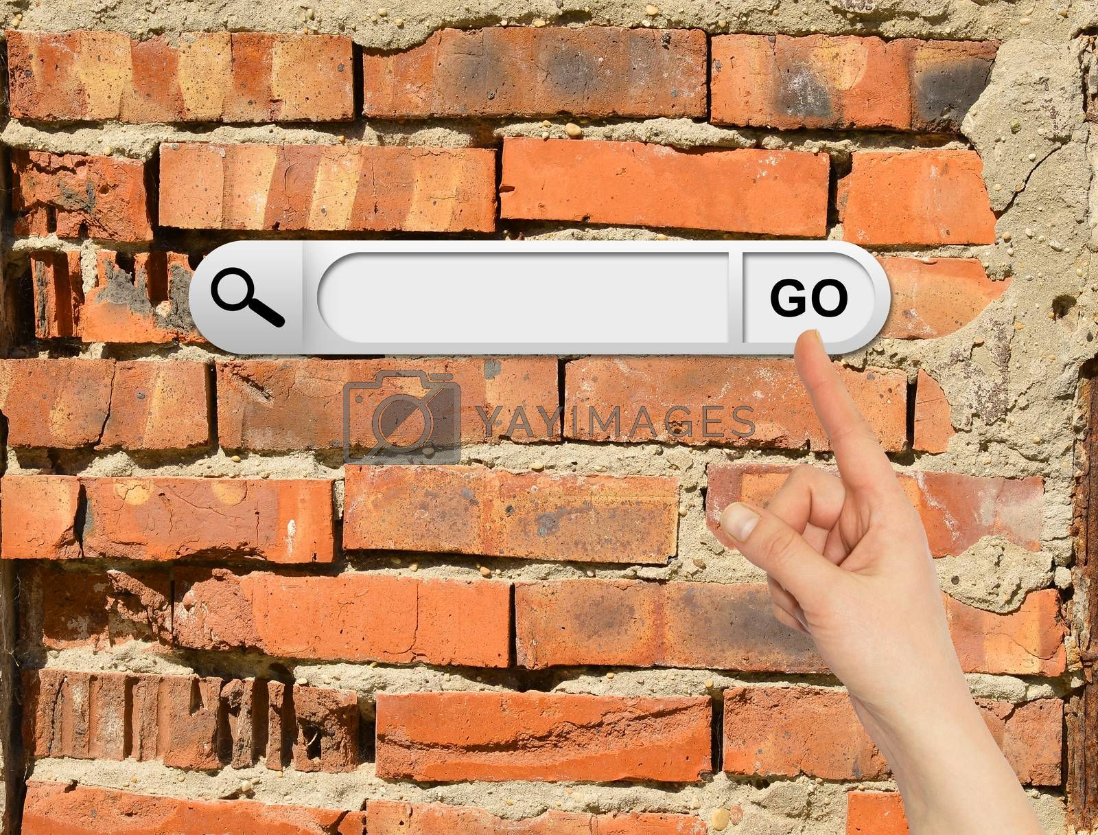 Human hand indicates the search bar in browser. Cracked bricks wall on background