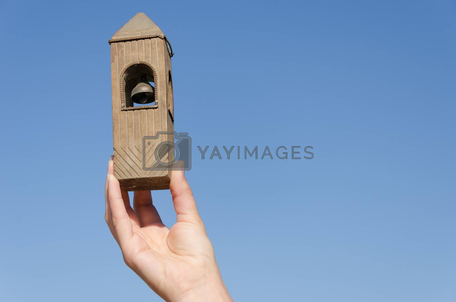 female hand hold old vintage wooden belfry miniature on blue sky background