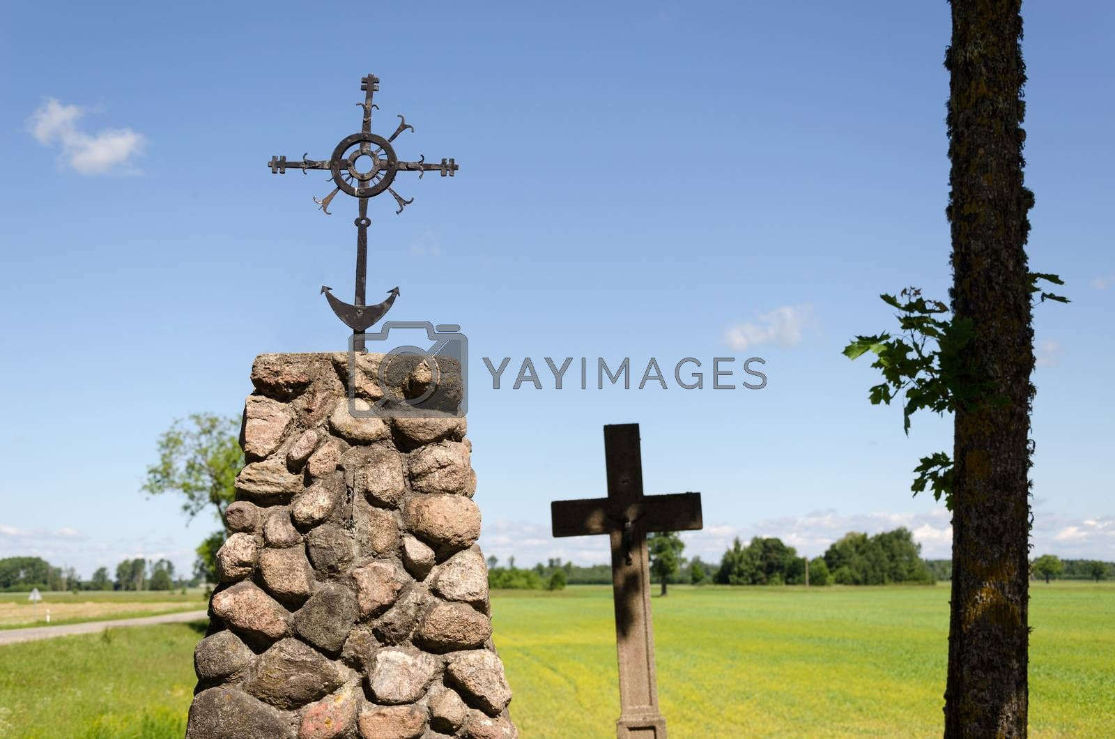 stone monument with metal ornament squirm cross in summer nature