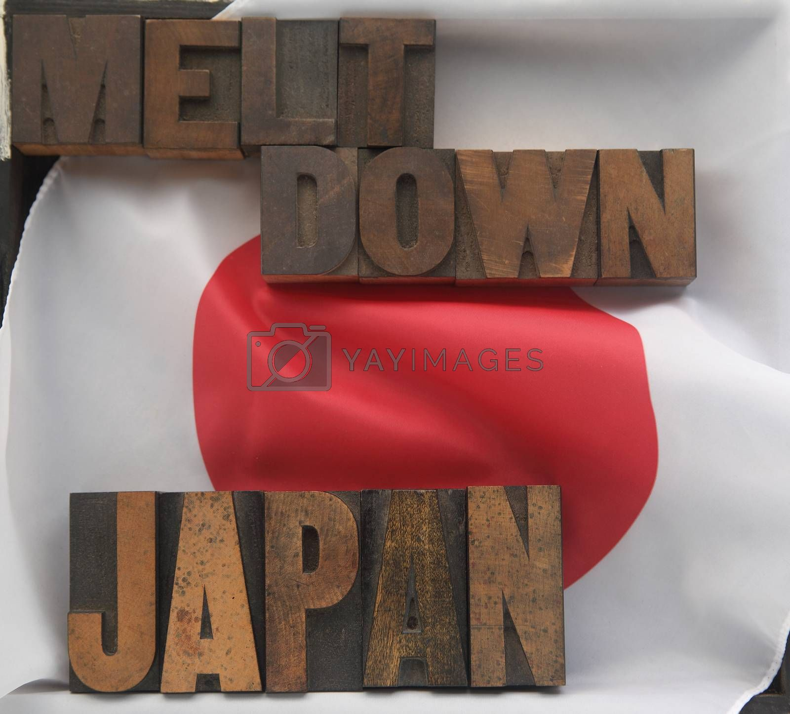 the words Japan and meltdown in old wood type on a Japanese flag