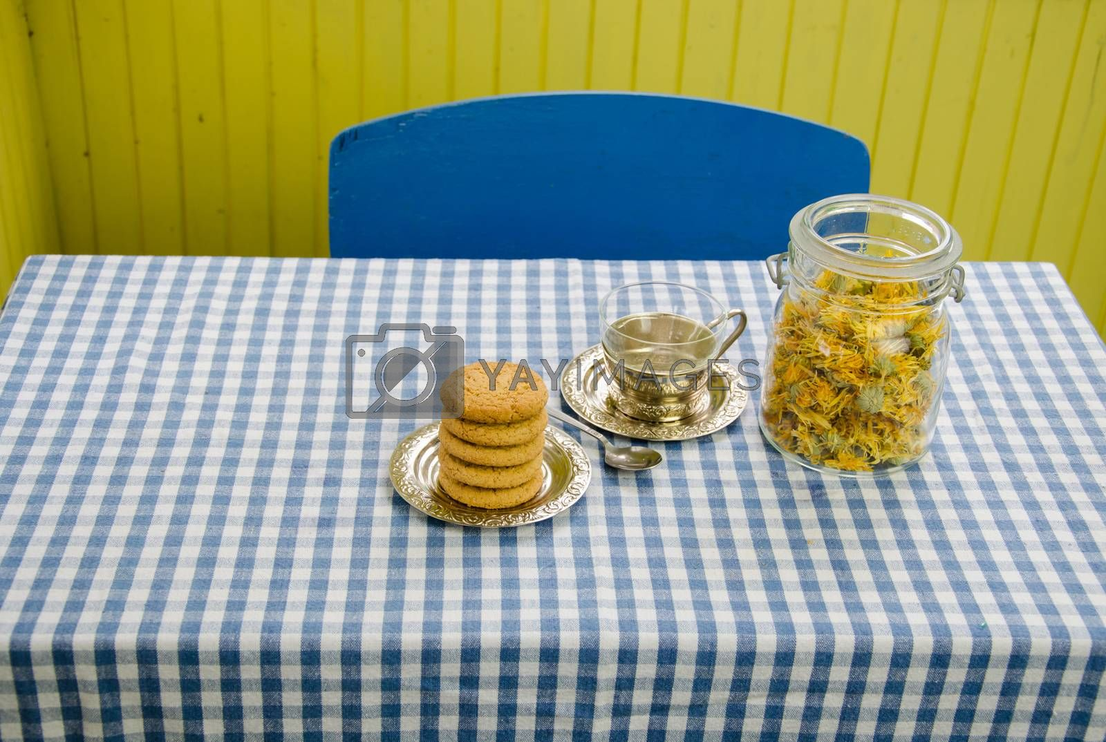 dried marigold flowers dish with antique cup and dietary cookies on the table