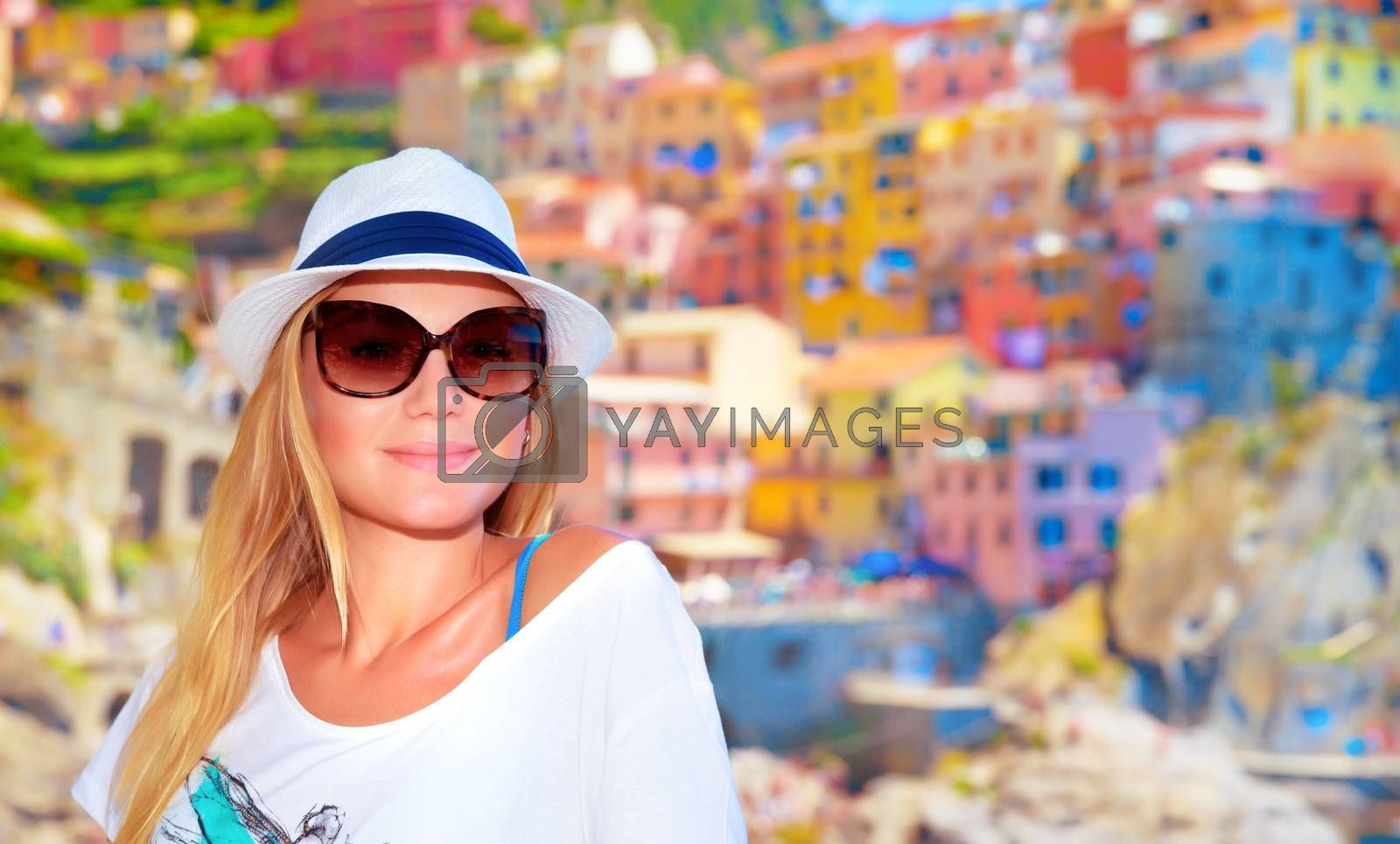 Attractive girl enjoying travel to Europe, standing on wonderful colorful buildings background, famous street in Cinque Terre