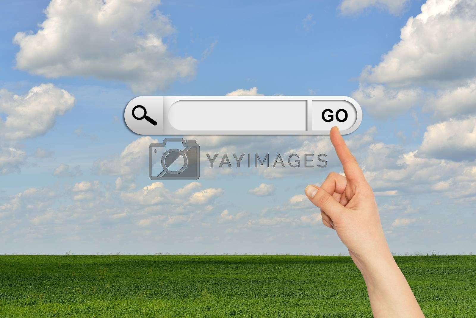 Human hand indicates the search bar in browser. Green grass and clouds on background
