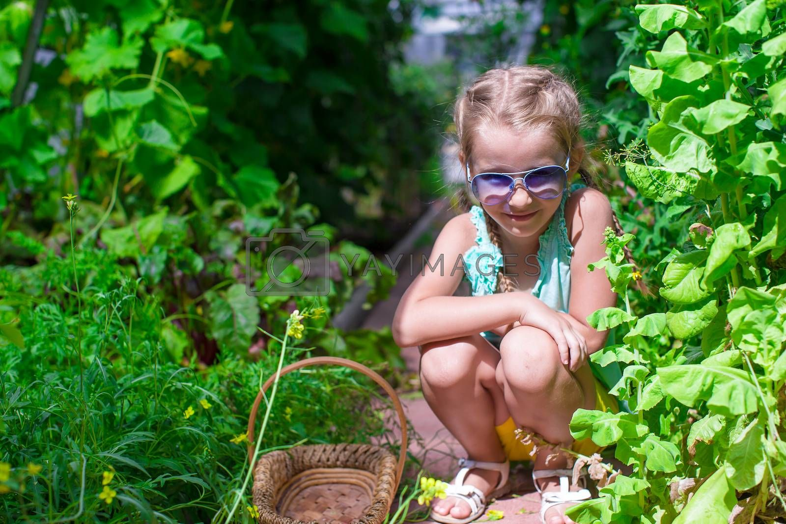 Cute little girls collects the crop onions in the greenhouse
