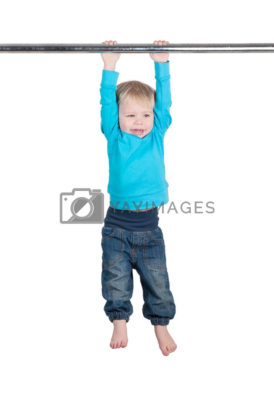 Portrait of a funny little boy hangs by horizontal bar