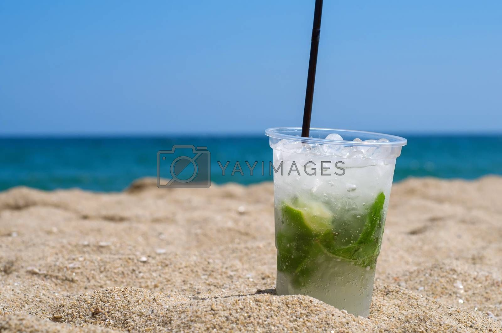 Mojito cocktail on the sandy beach and sea on the background