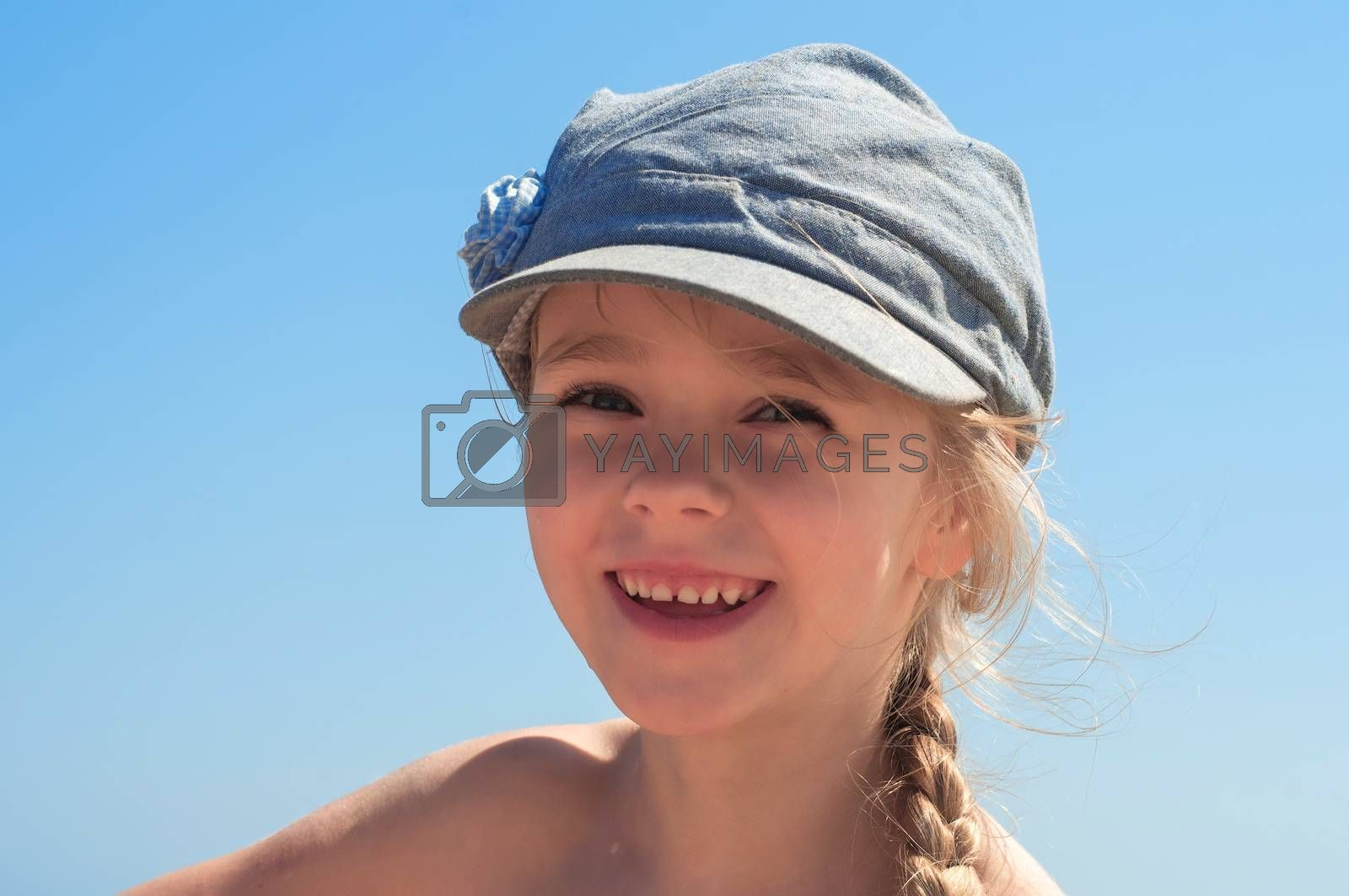 Adorable happy little girl in denim cap on the beach