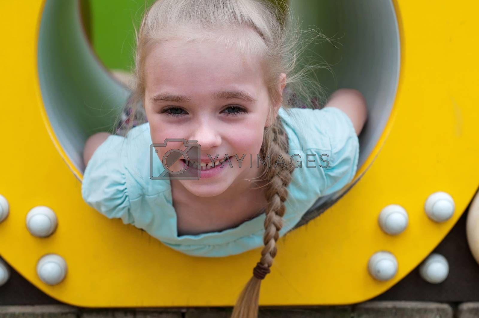 Adorable young girl sitting in crawl tube on the playground