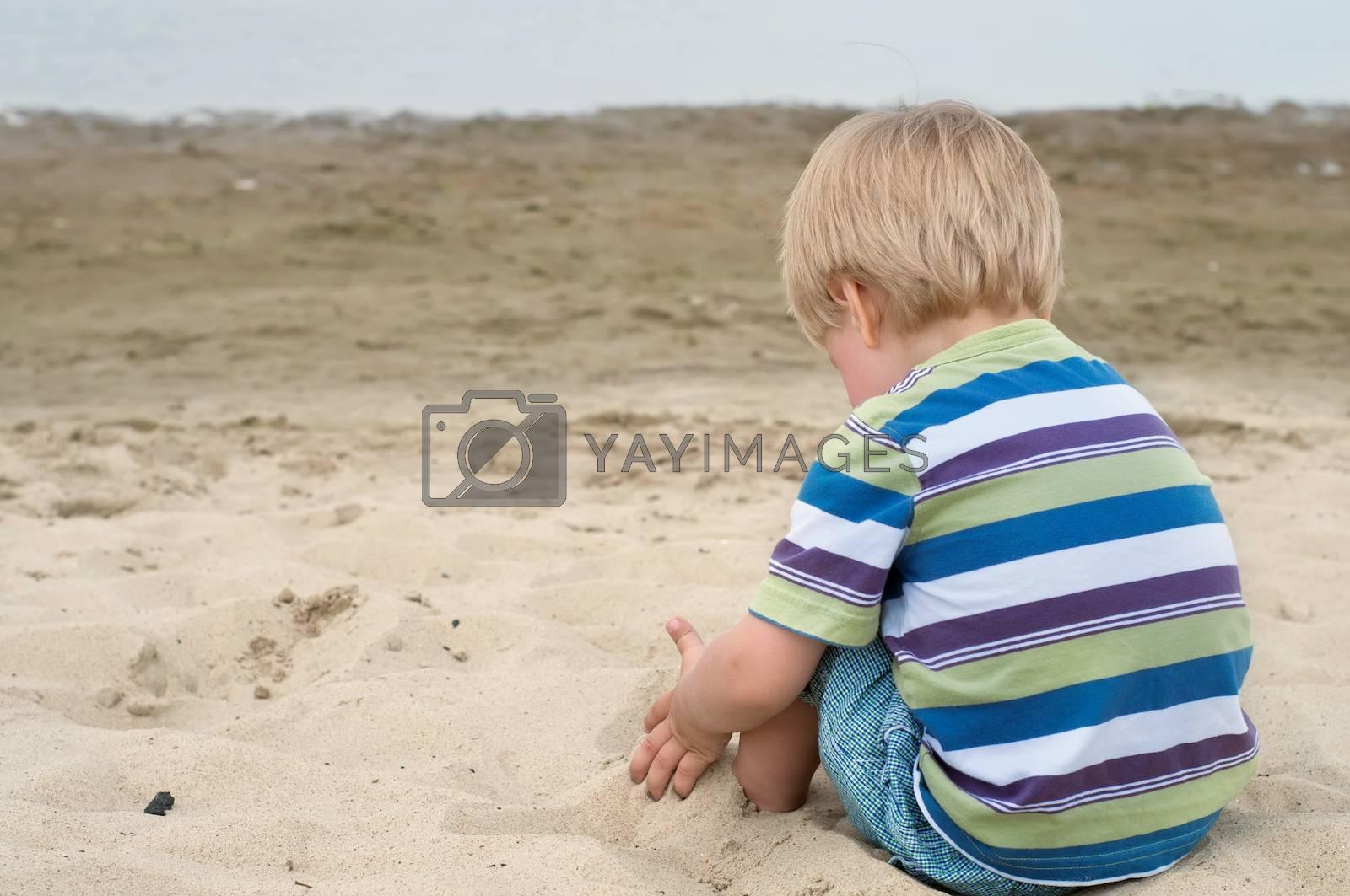 Little toddler boy in striped t-shirt sitting back on sandy beach
