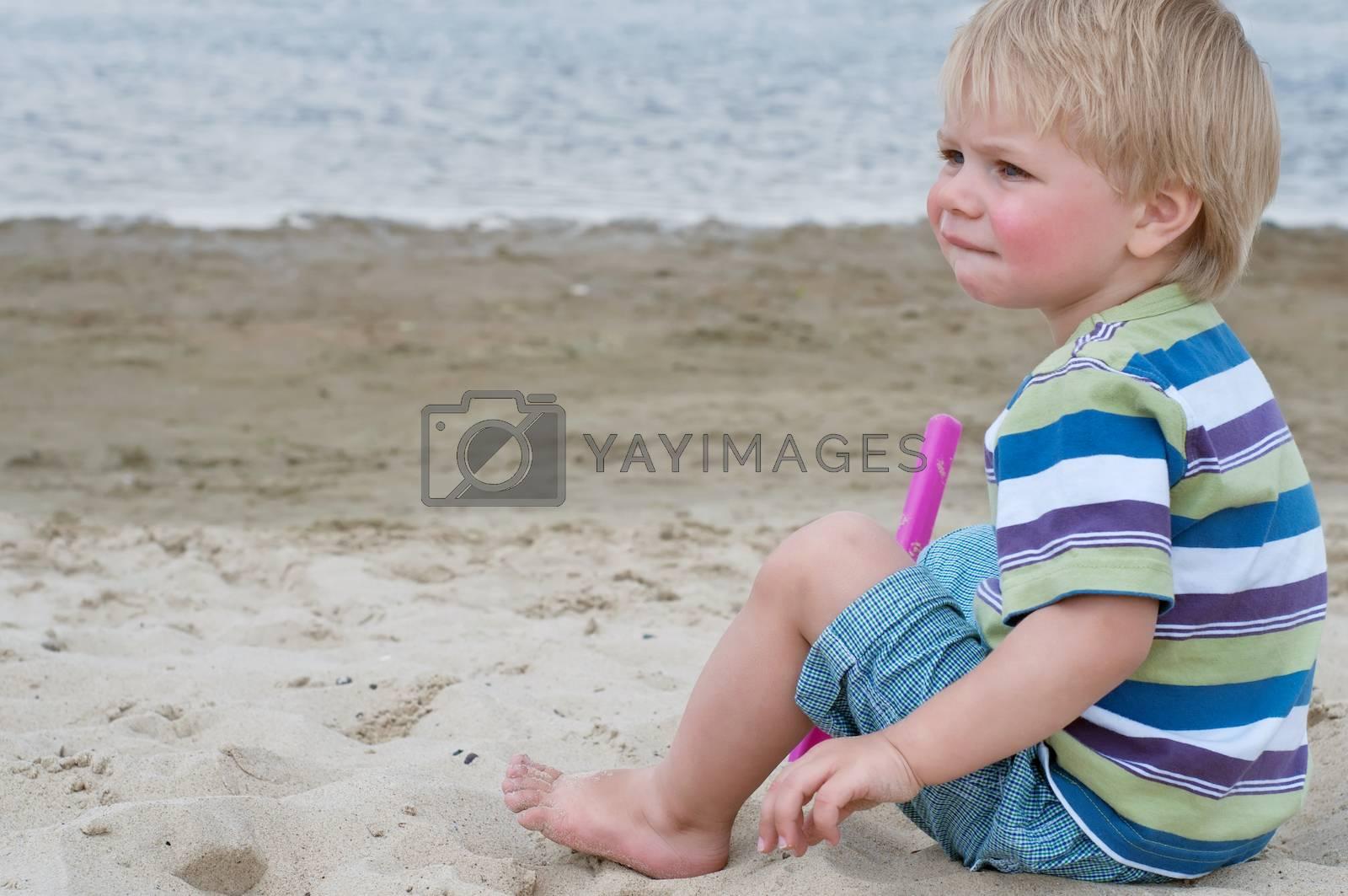 Little toddler boy in striped t-shirt sitting on sand beach