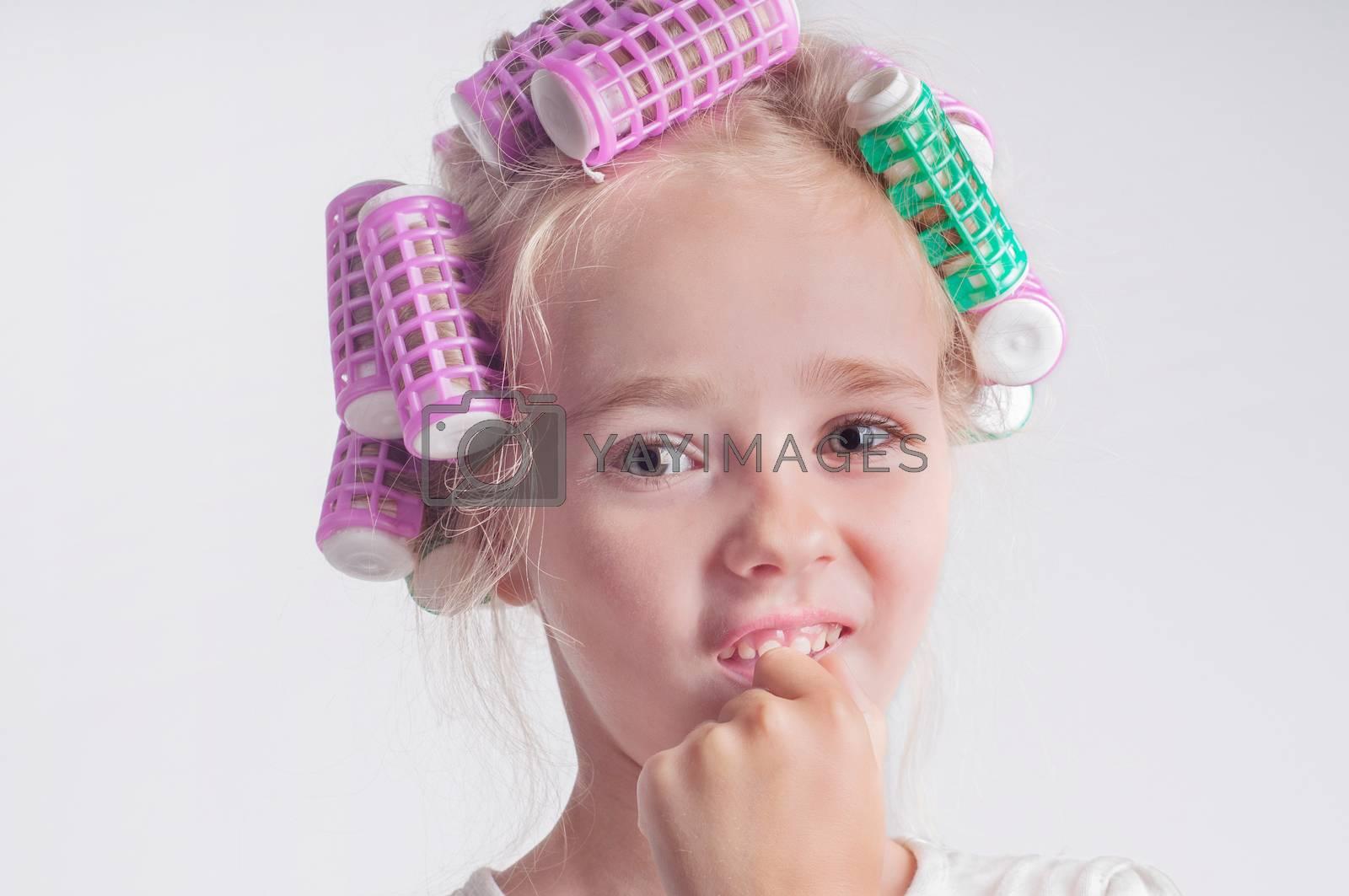 Cute child girl portrait in curlers, studio