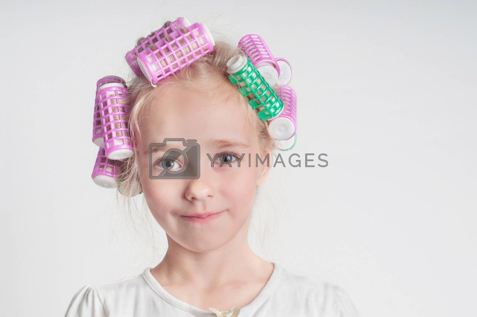 Adorable child girl portrait in curlers, studio