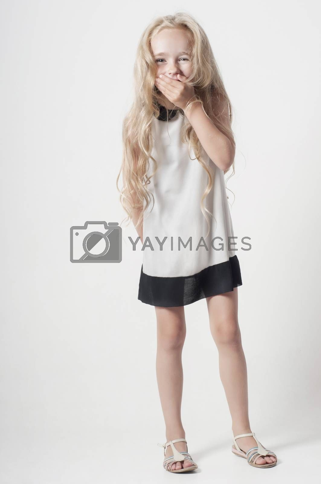 Little girl in white dress covers her mouth with her palm