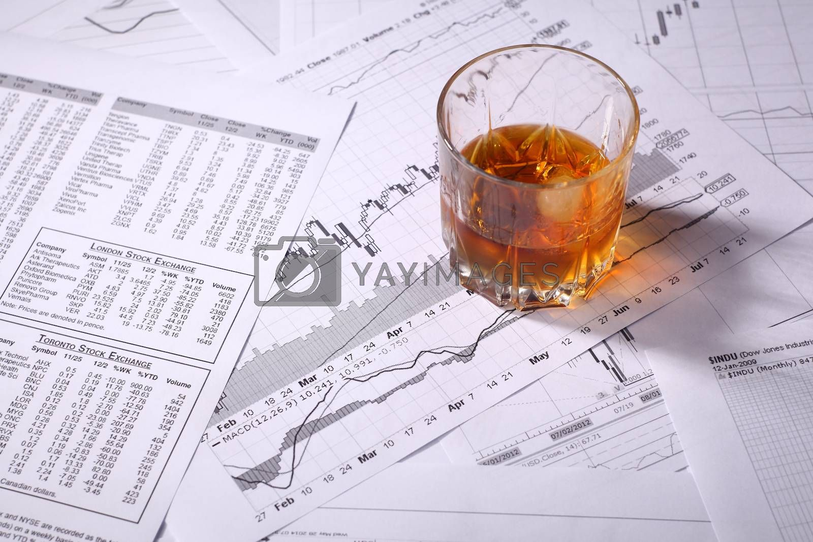 Royalty free image of Glass of whiskey on charts by hiddenhallow