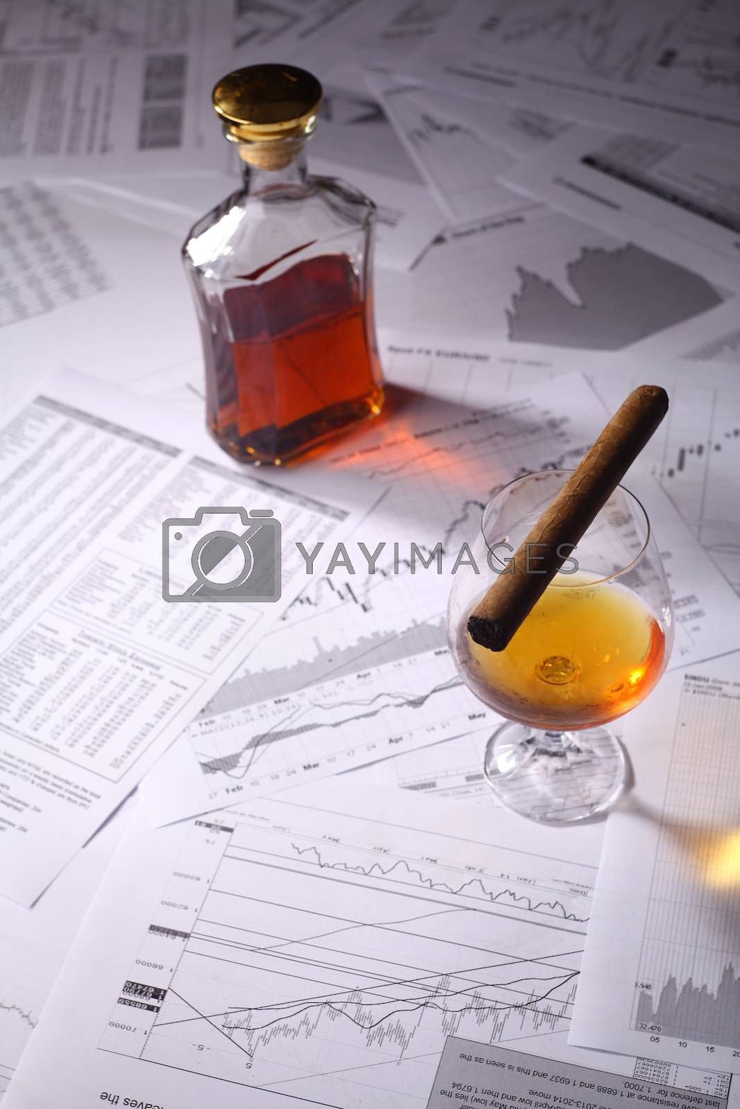 Royalty free image of Brandy and cigar on charts by hiddenhallow