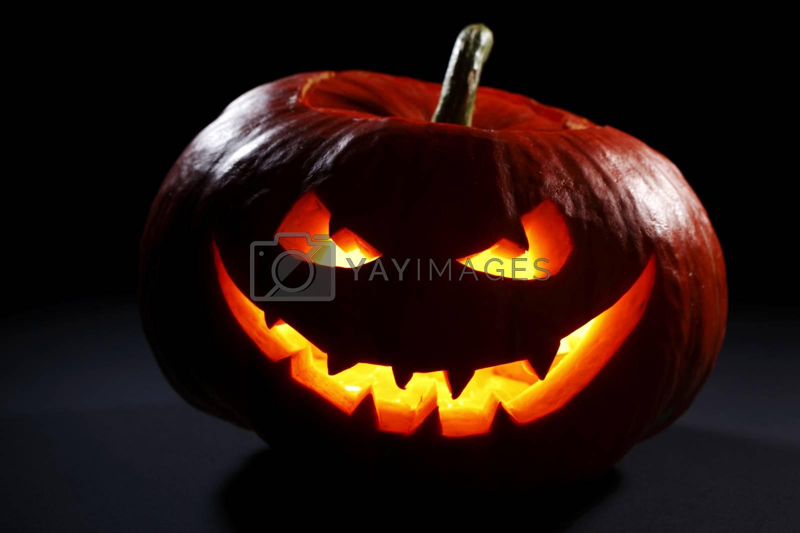 Halloween pumpkin head jack lantern with scary evil face on black