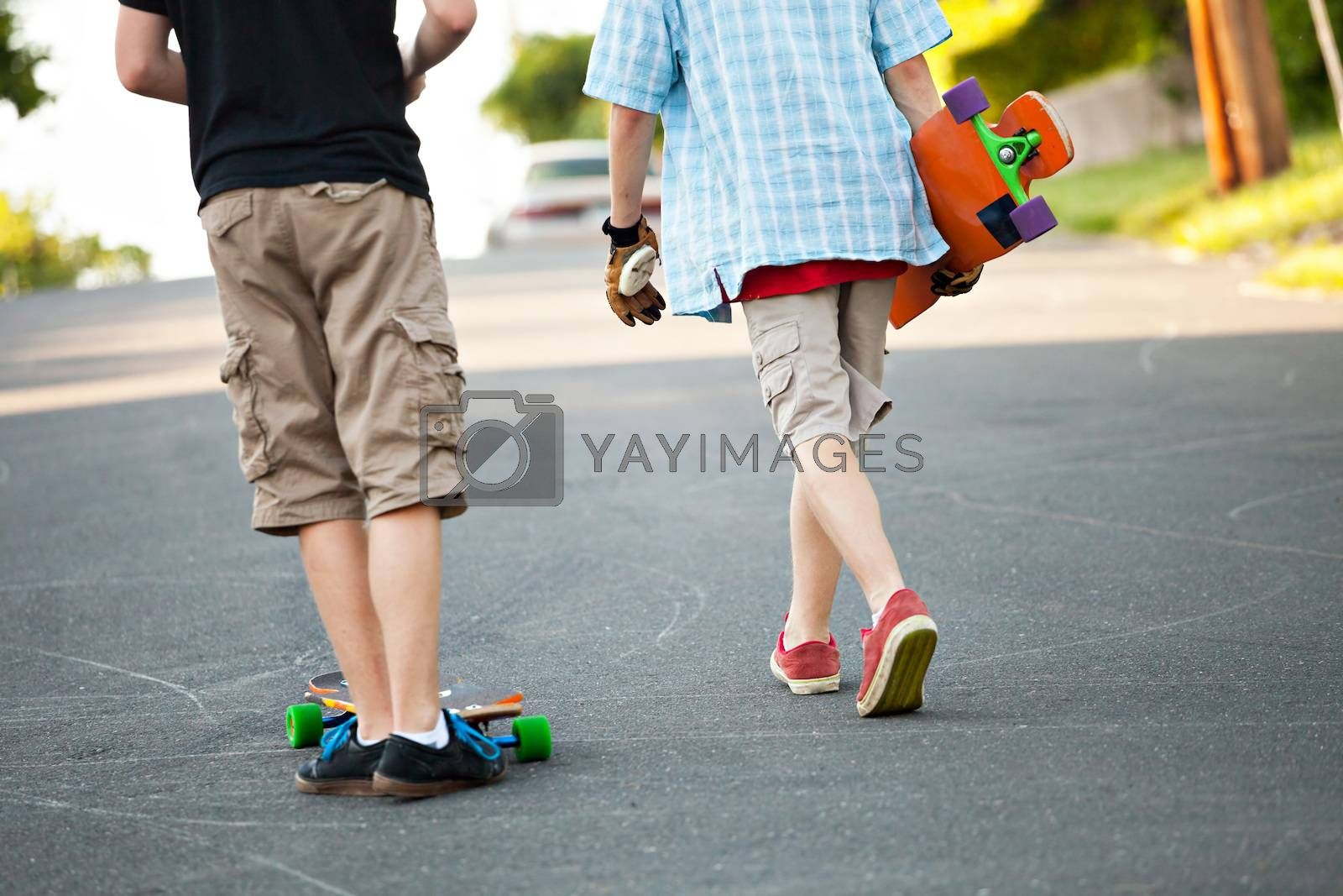 Close up of some long boarders on an urban road.