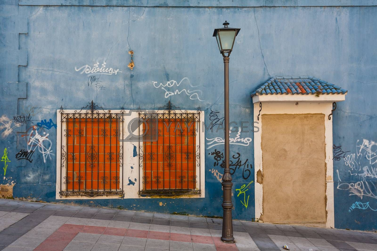 Curiosus image of a bricked up house with lamppost and graffitis in the street Salamance Spain