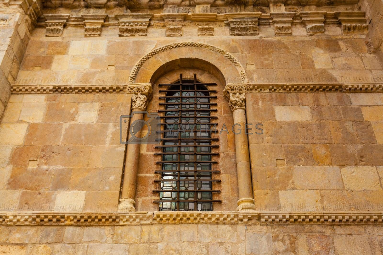 Delightful romanesque art window along with forged protection in the wall of the San Isidoro collegiate church in Leon ,Spain