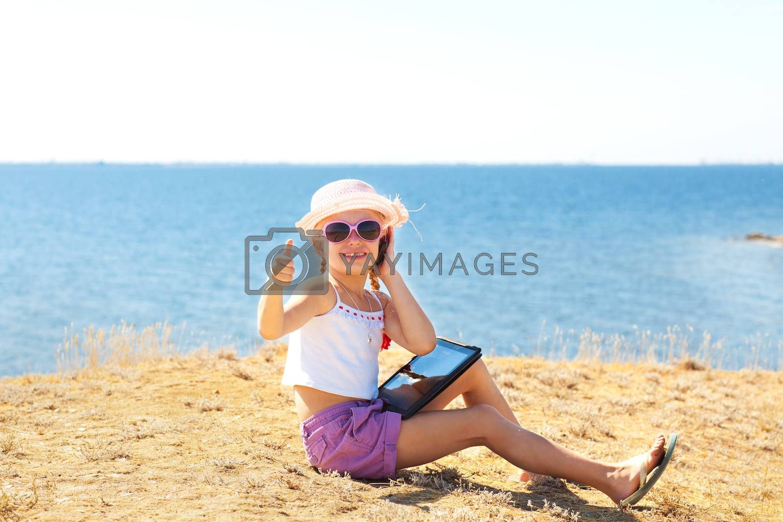 girl on the beach with laptop and phone showing okay