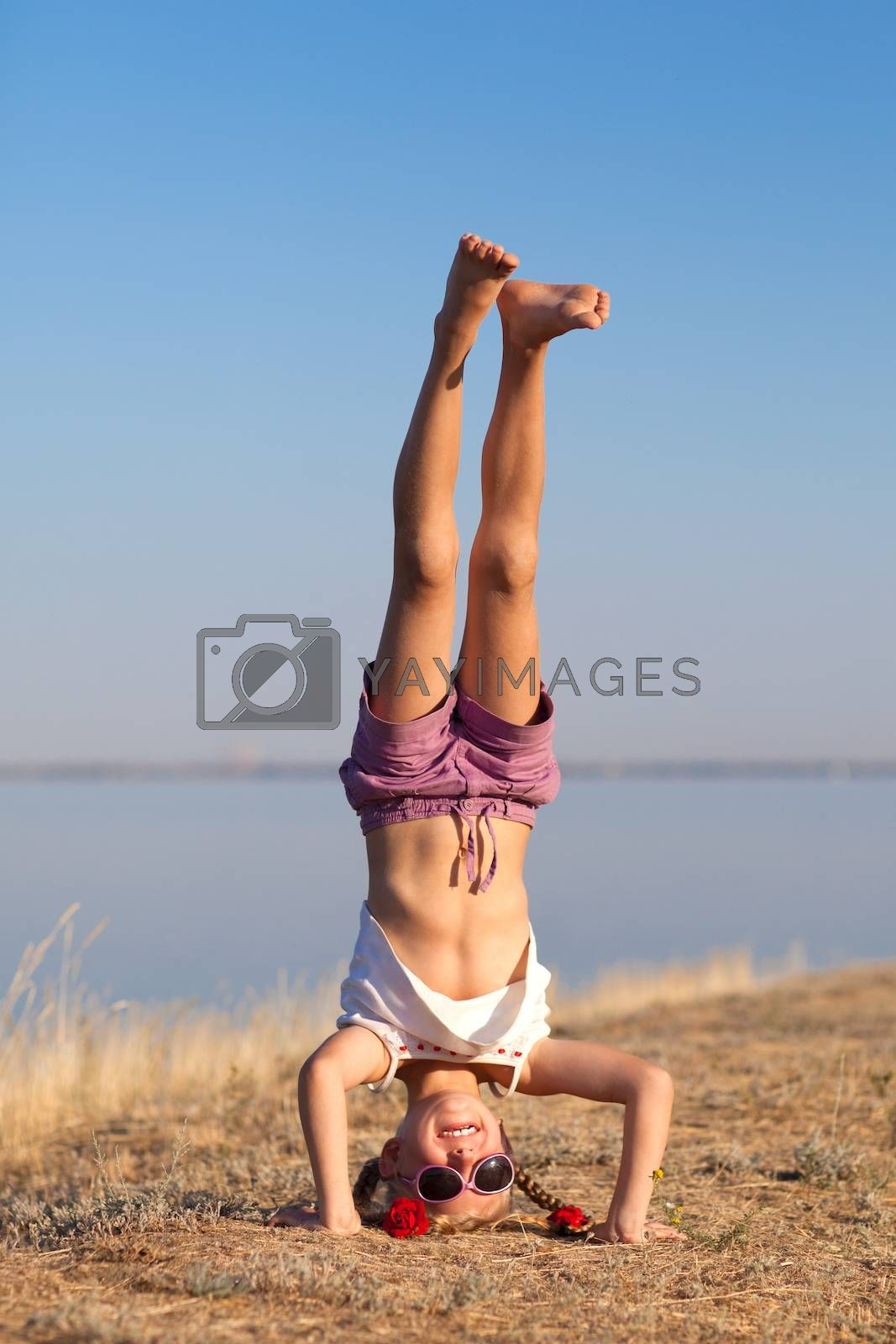 girl doing head stand on the beach