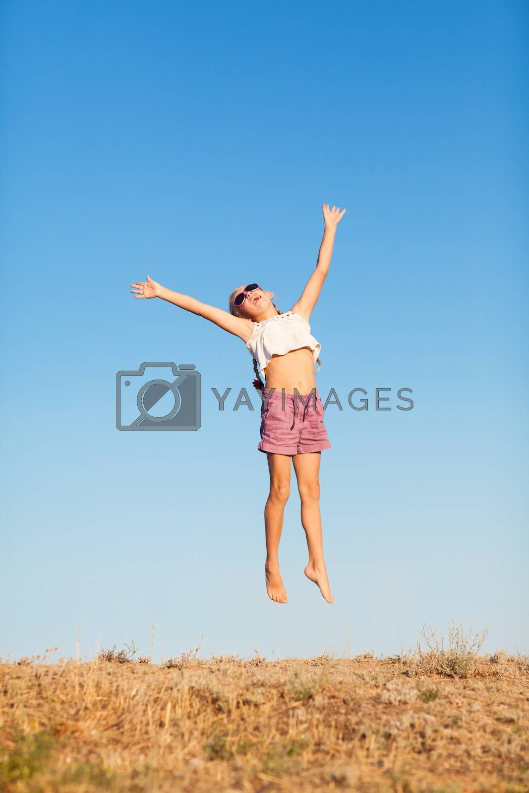 happy small girl jumping outdoors