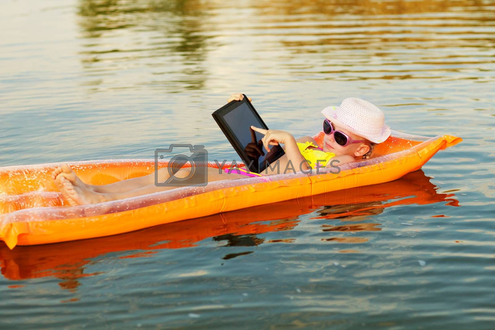 girl on the swimming mattress with laptop