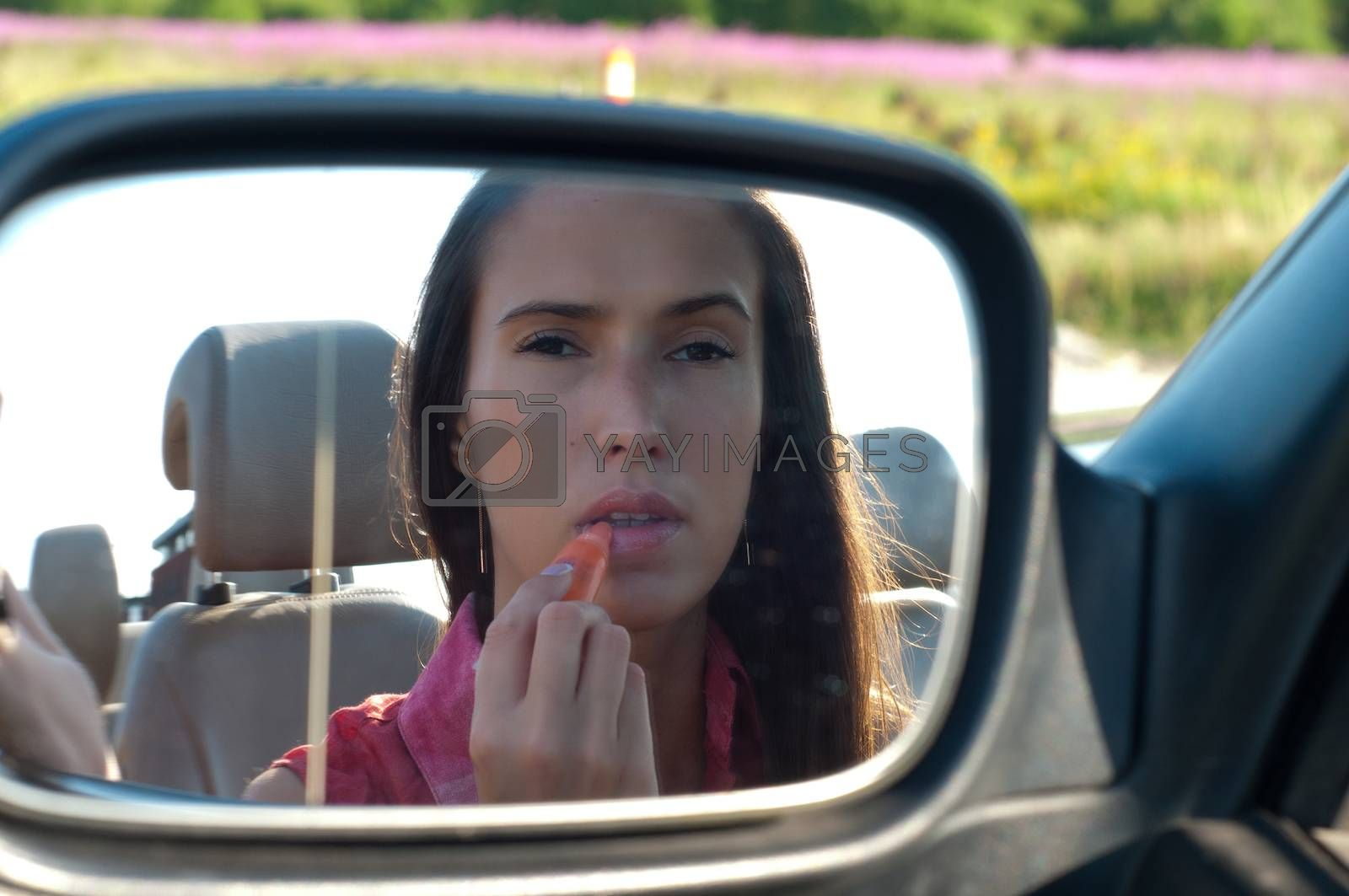Young caucasian woman applying lipstick looking at reflection in car mirror