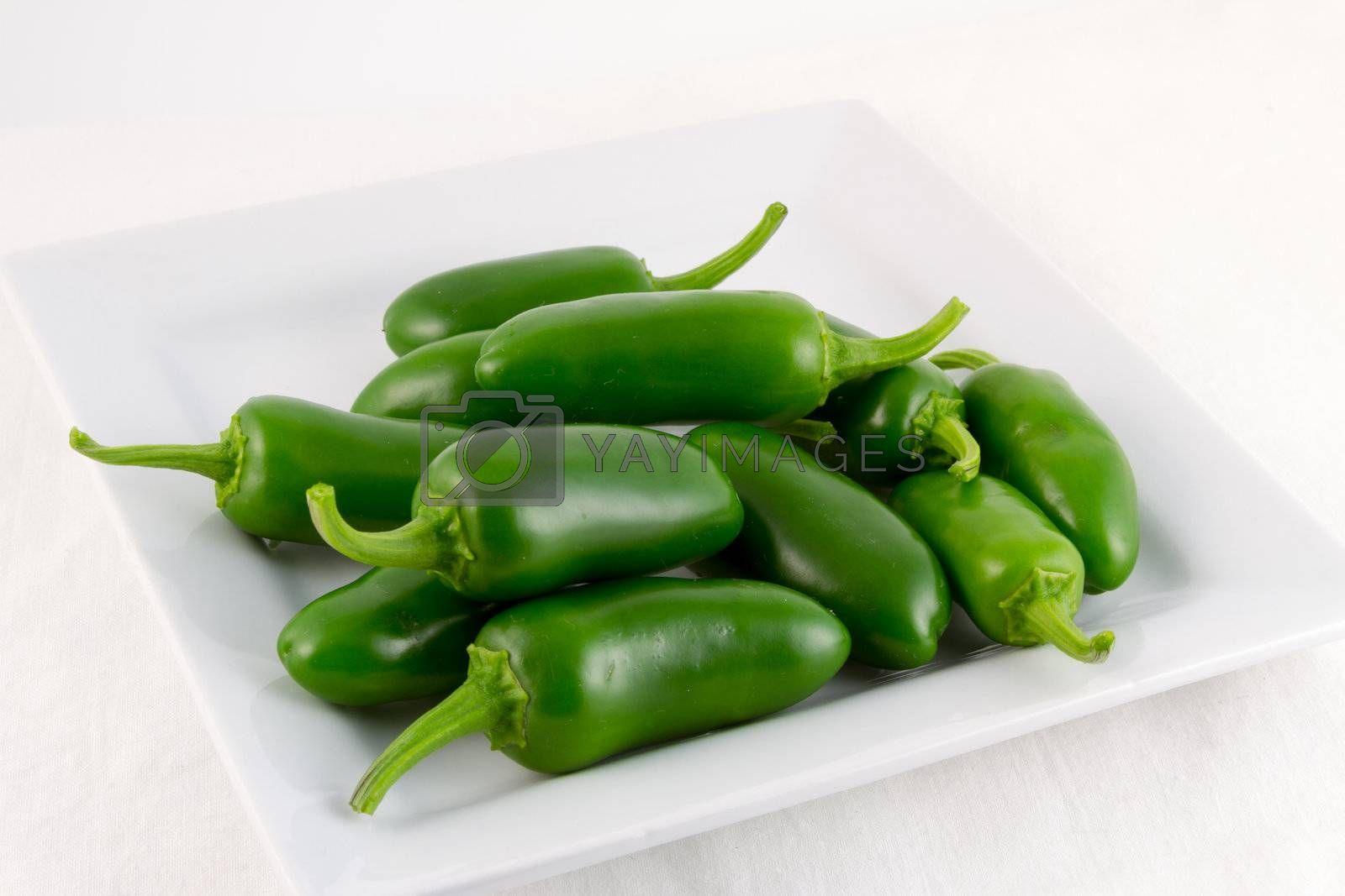 A group of freshly picked green Padron chilis on a square white plate with white background
