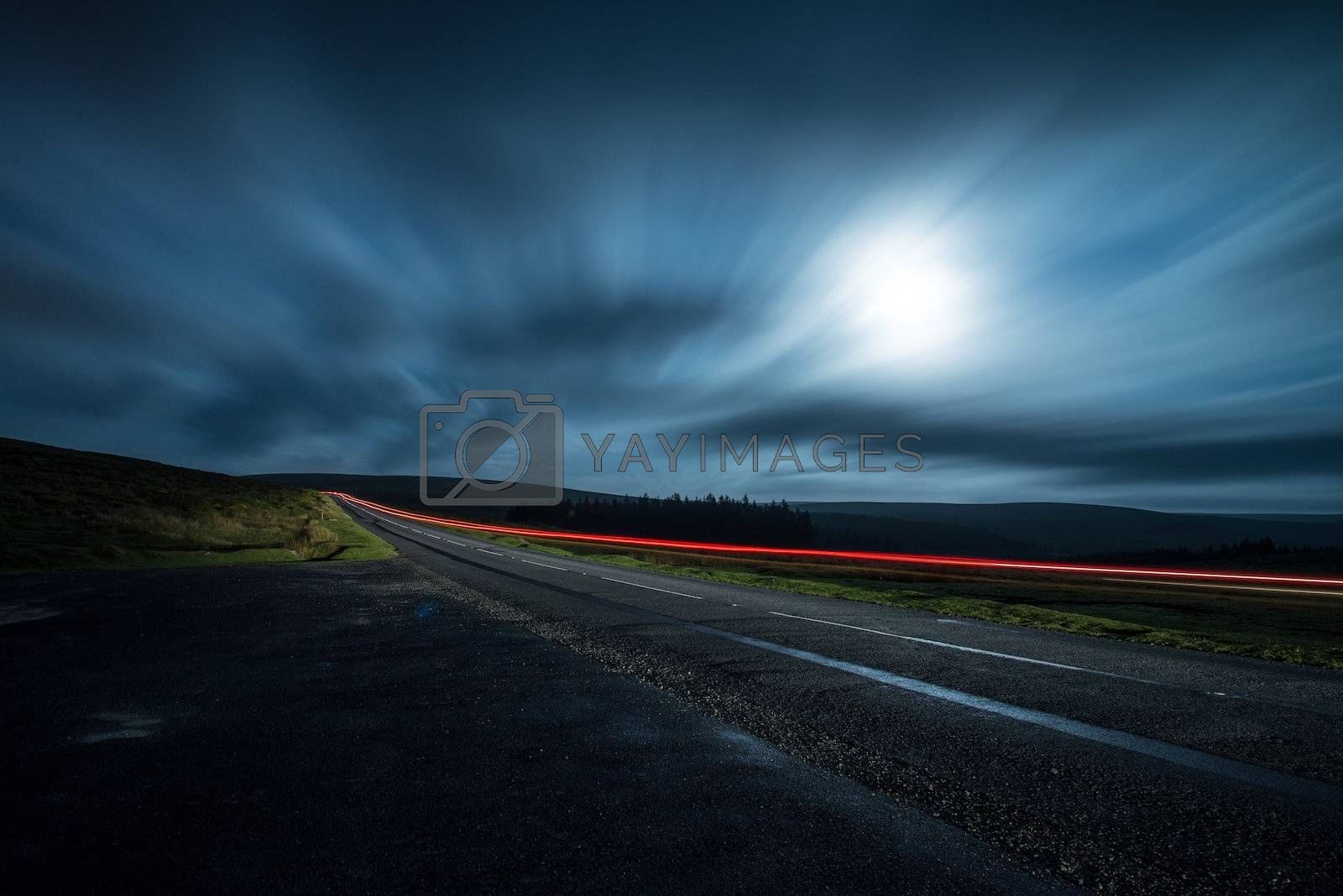 blur night shoot of fast driving car with blured clouds and moon