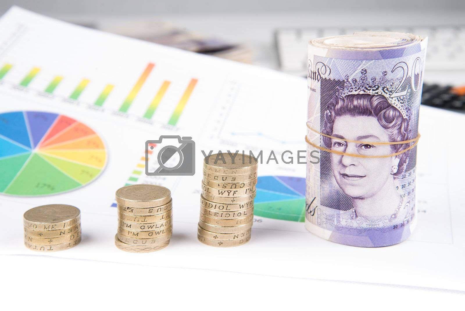 British pound sterling coins and notes with financial chart in background