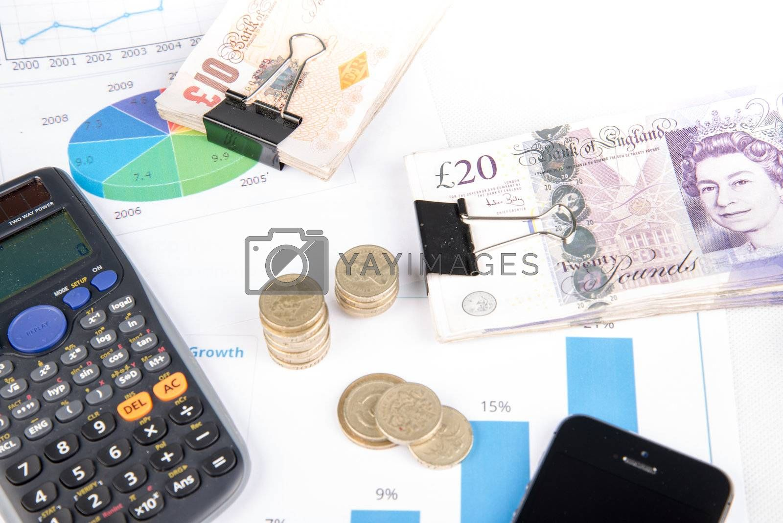 British pound sterling coins and bank notes on desk with keyboard and financial chart