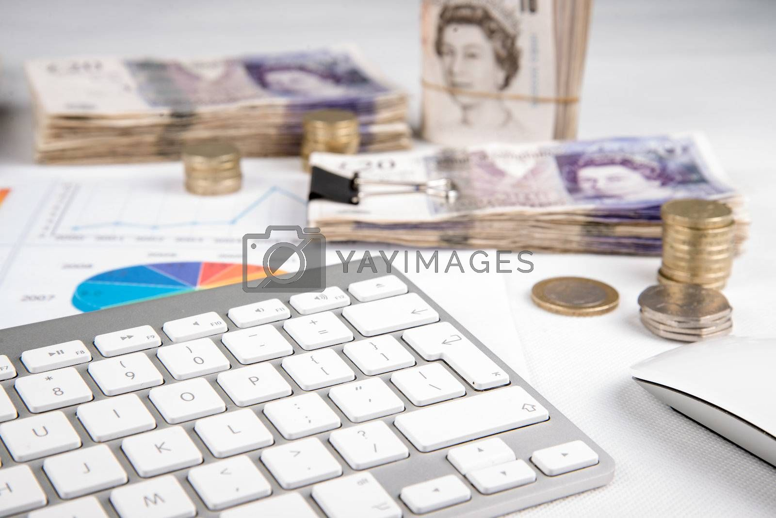British pound sterling coins and bank notes on desk with keyboard
