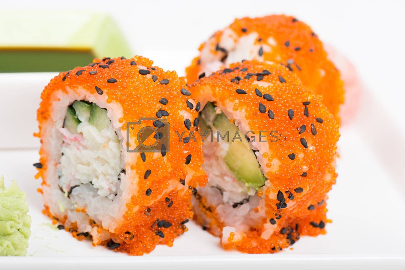 Sushi rolls with orange tobico on the plate
