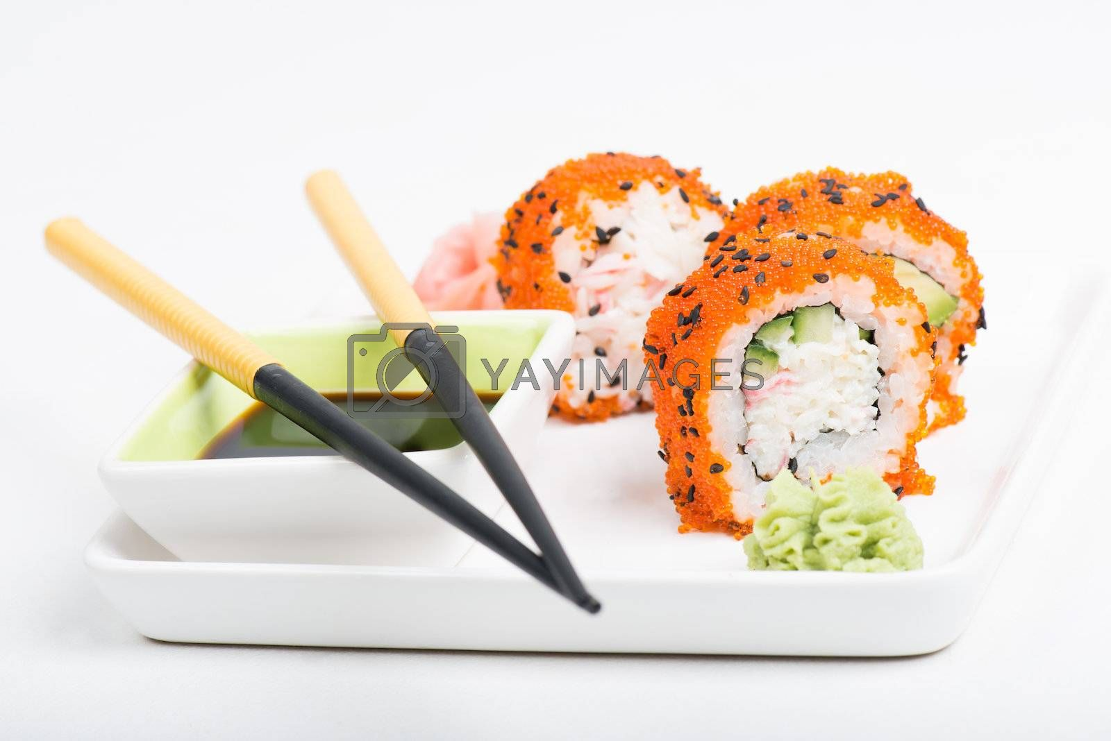 Chopsticks and sushi on the plate, light background