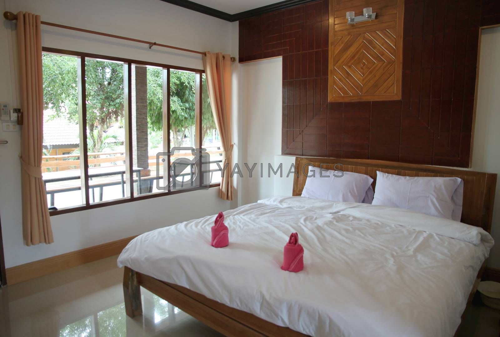 wooden bedroom have a white bedding.