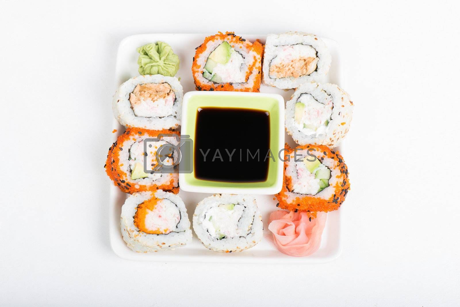 Different sorts of sushi rolls with soy sauce on the plate