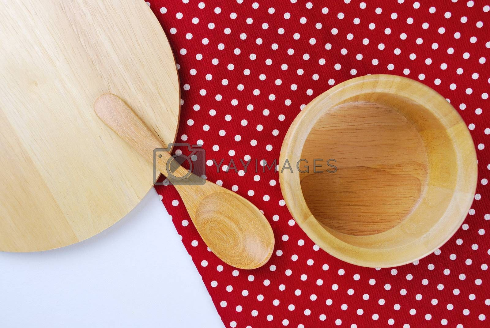 Royalty free image of Wooden bowl, tablecloth, spoon, fork on table background  by teen00000