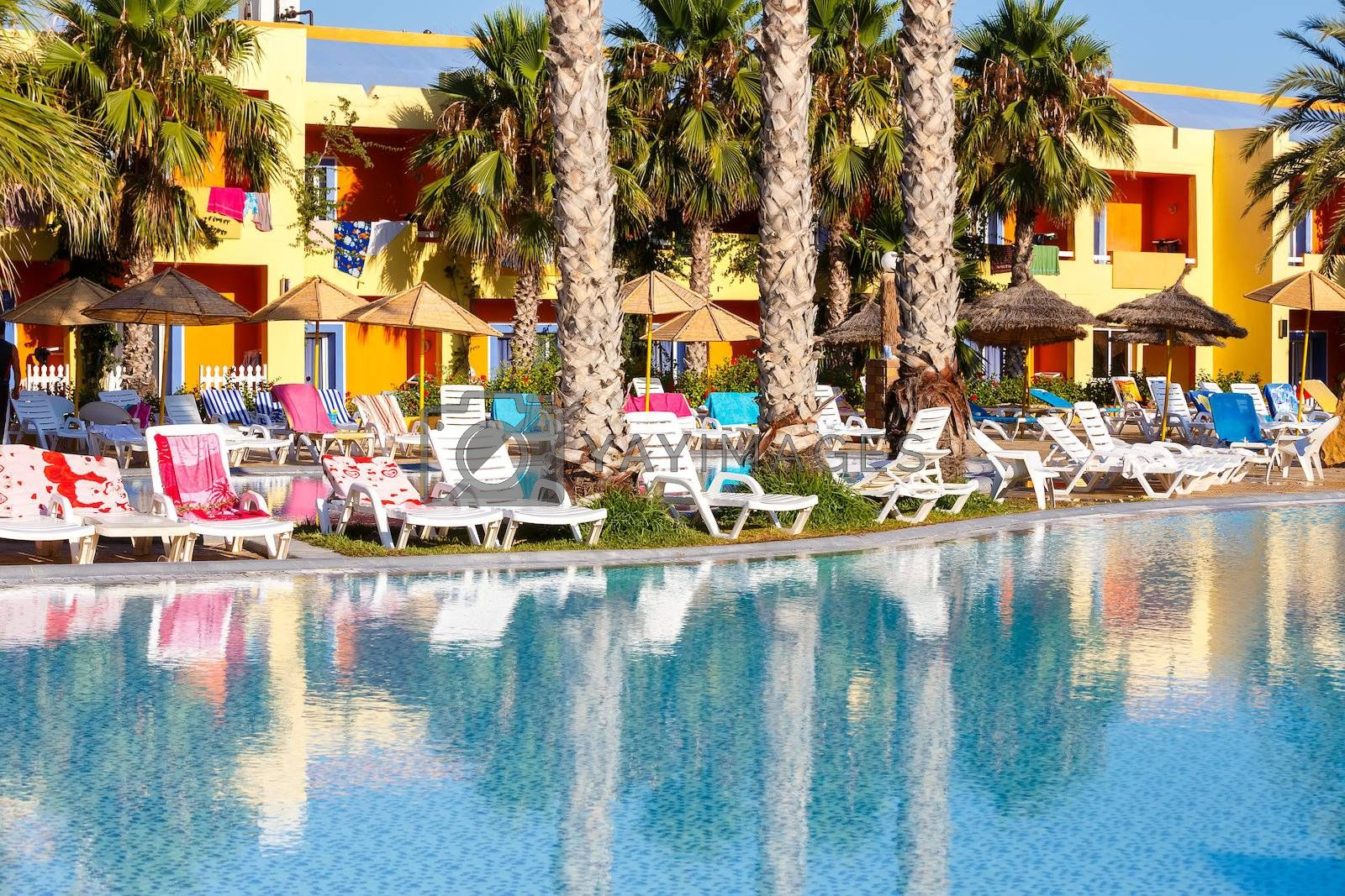 Royalty free image of sunloungers on swimming pool  by artush