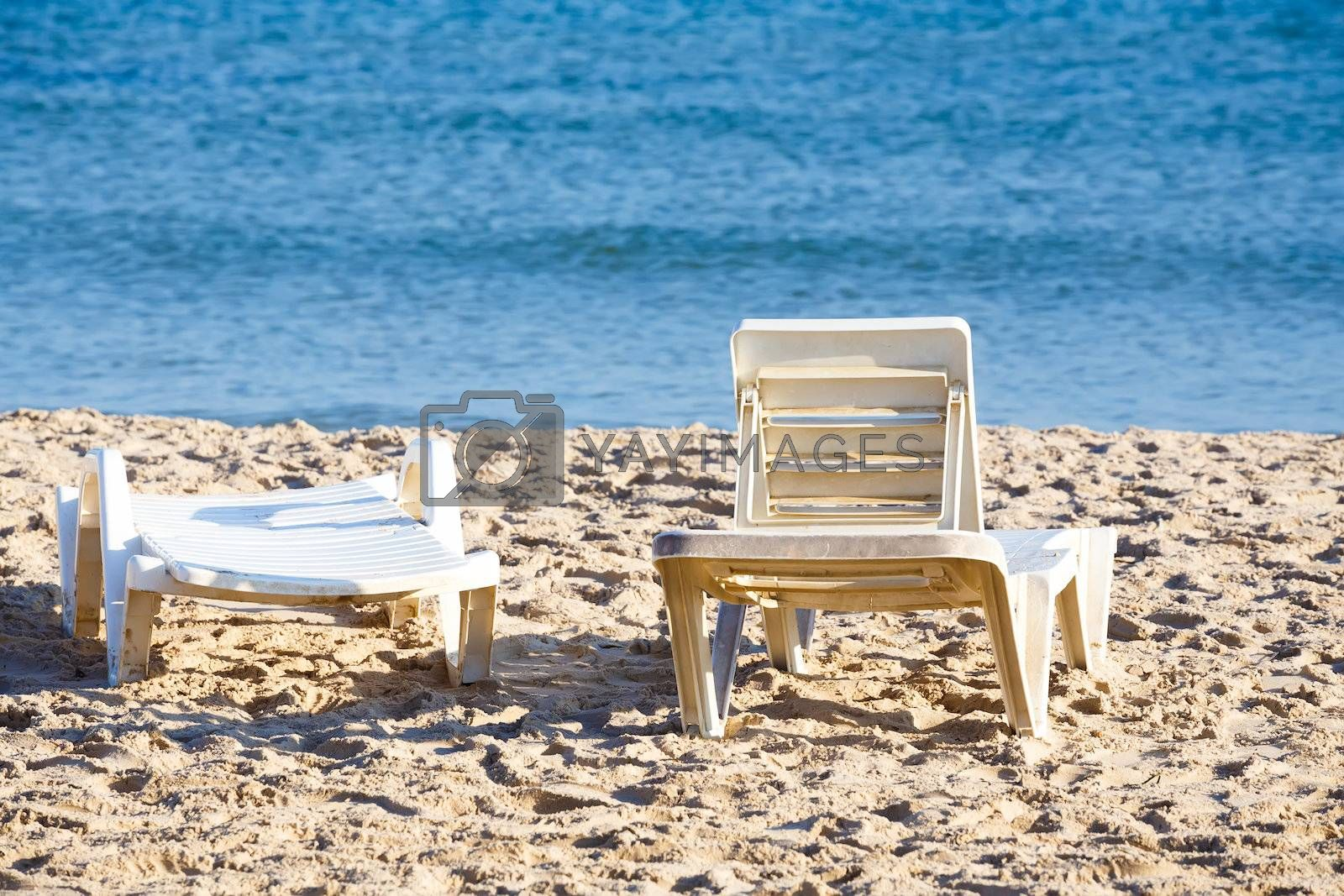 Royalty free image of two old sunloungers on tunisian beach by artush