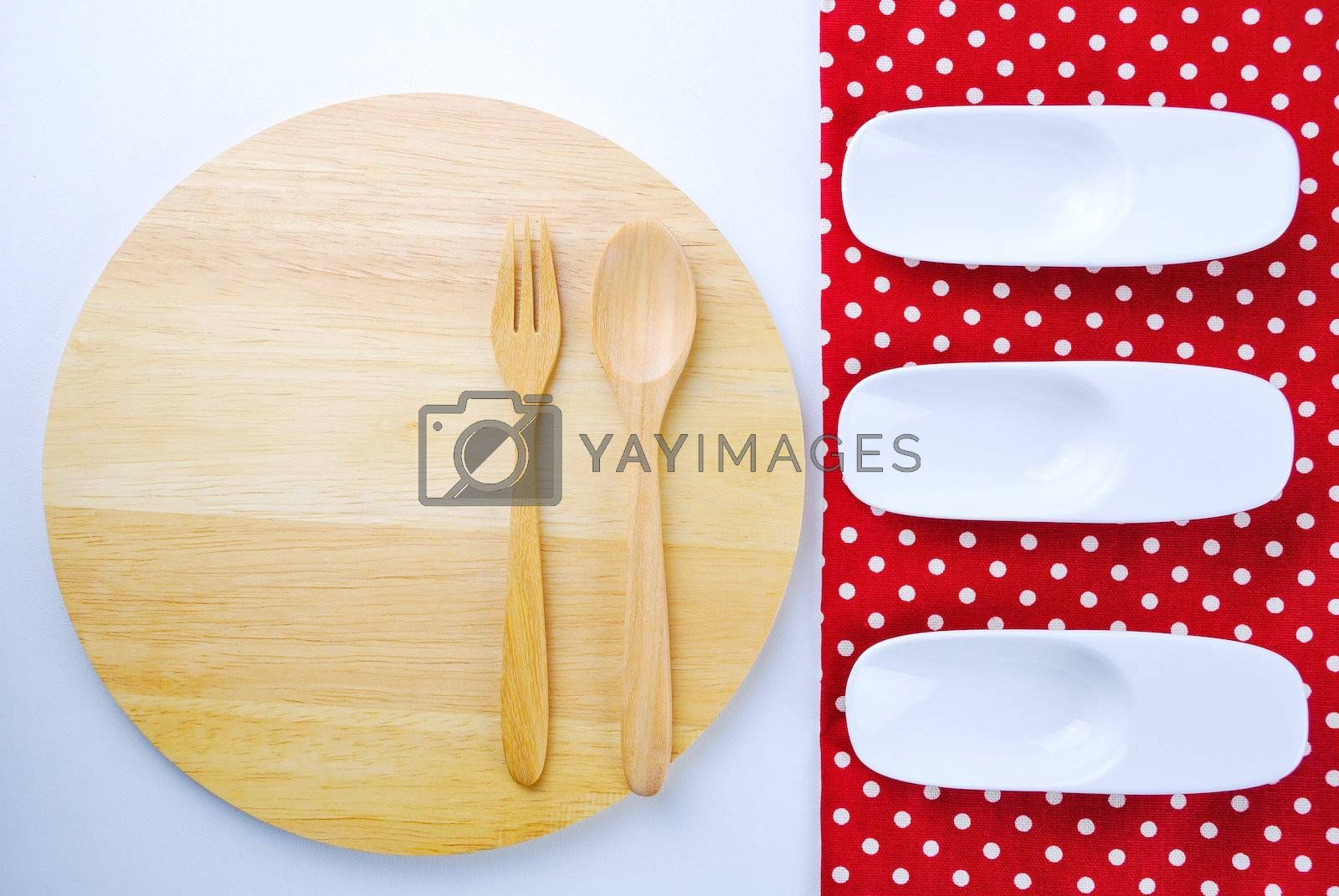 Royalty free image of Wooden plate, tablecloth, spoon, fork on table background  by teen00000
